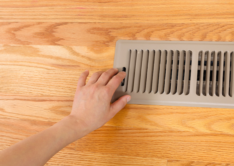 Horizontal photo of female hand opening up heater floor vent with Red Oak Floors in background